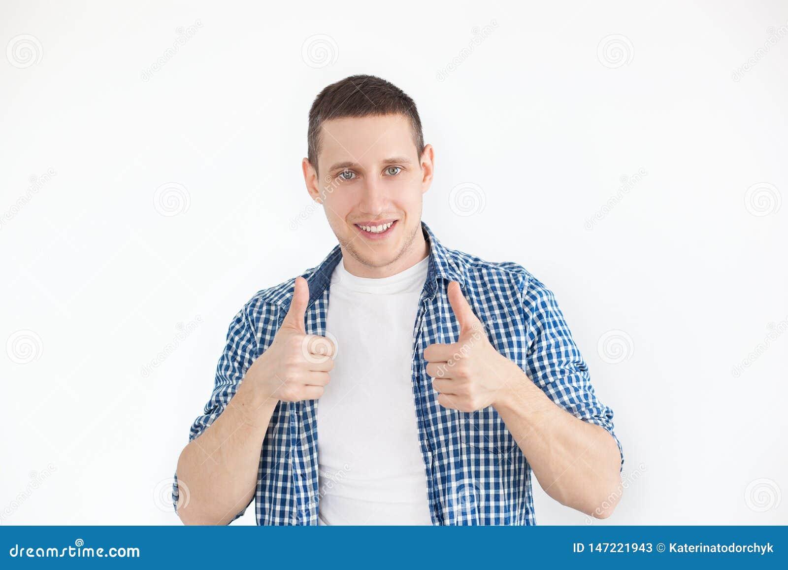 Het gelukkige knappe mens tonen beduimelt omhoog Een modieuze mens in een overhemd heeft het glimlachen eruit zien, adverteert ee