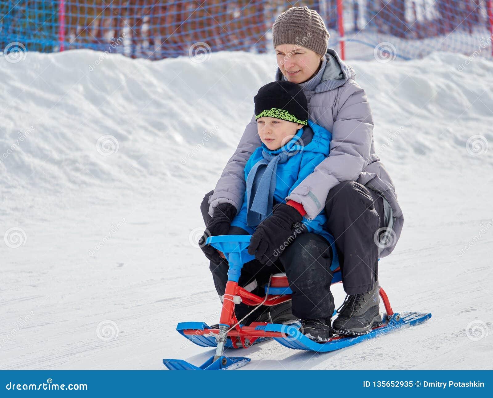 Het gelukkige mamma met zoon berijdt een slee van berg