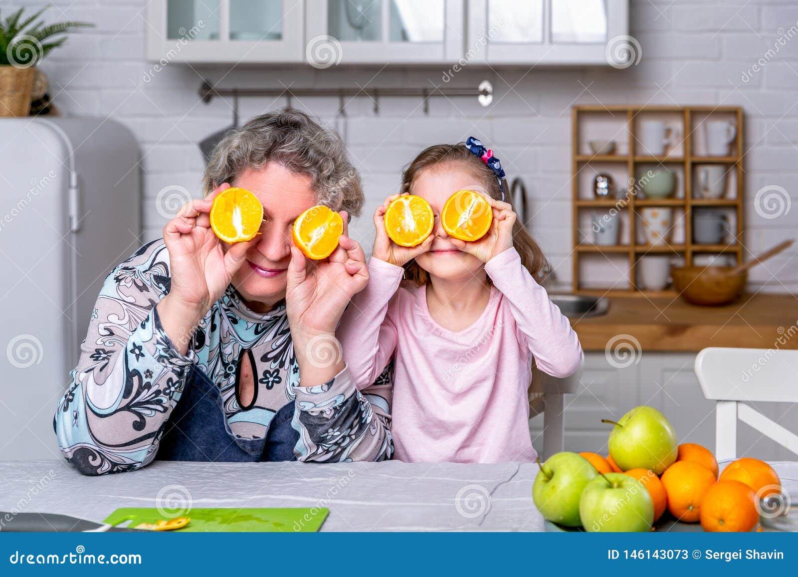 Het gelukkige meisje en haar grootmoeder hebben samen ontbijt in een witte keuken Zij hebben pret en spelen met vruchten