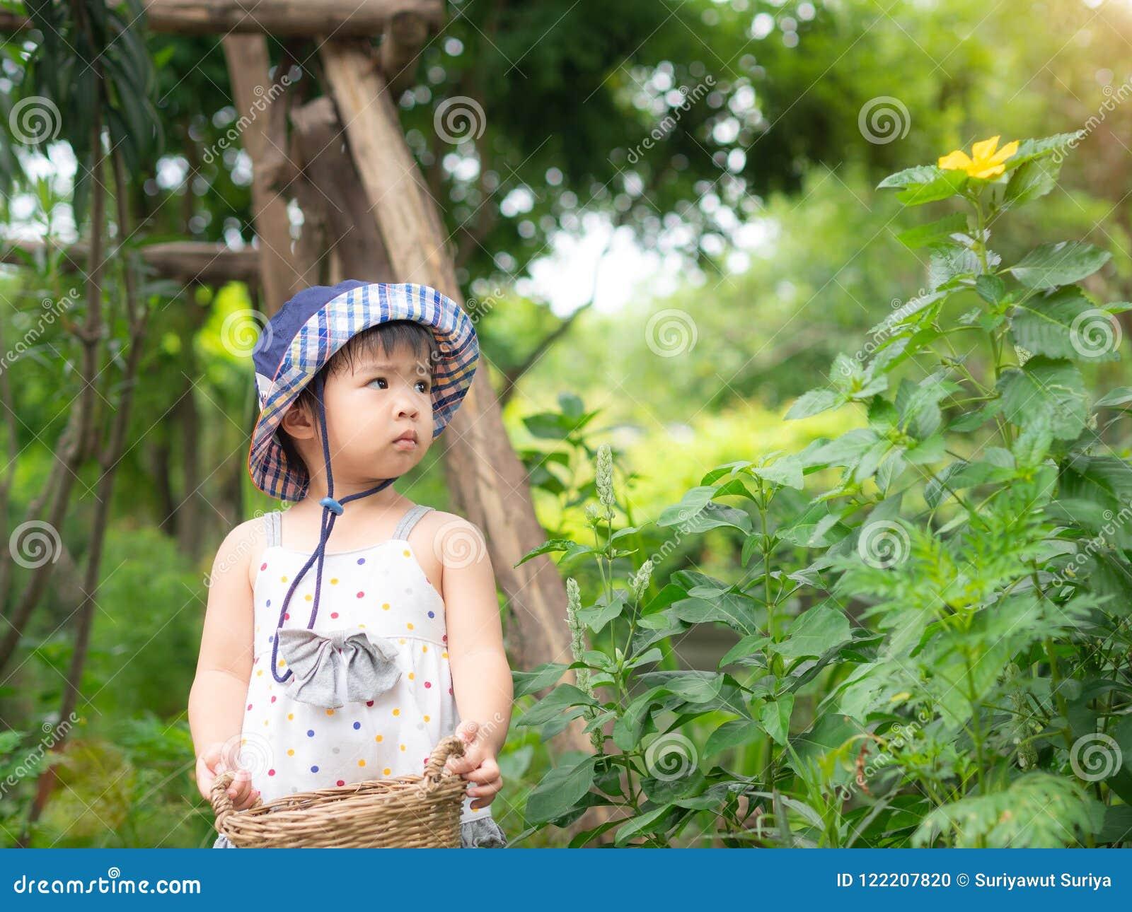 Het gelukkige meisje houdt de mand in het landbouwbedrijf De landbouw & Childre