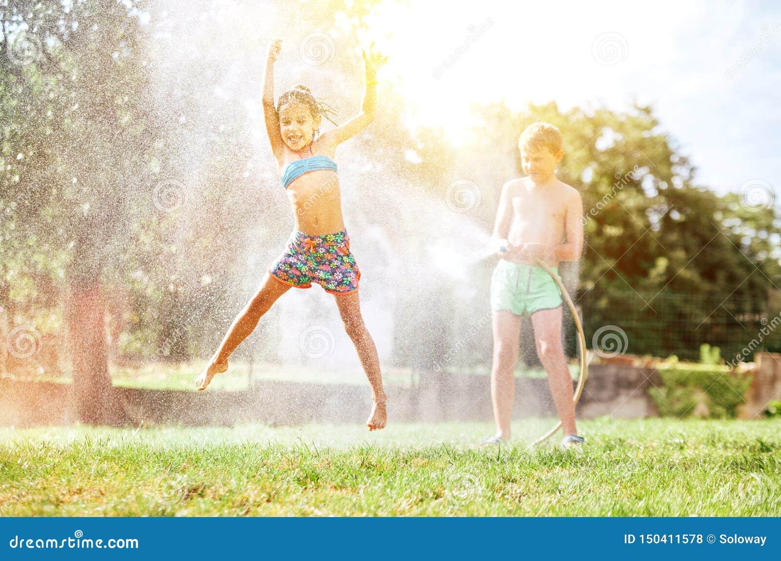 Het gelukkige meisje springt onder water, wanneer de broer haar van tuinslang giet De hete activiteit van de zomerdagen