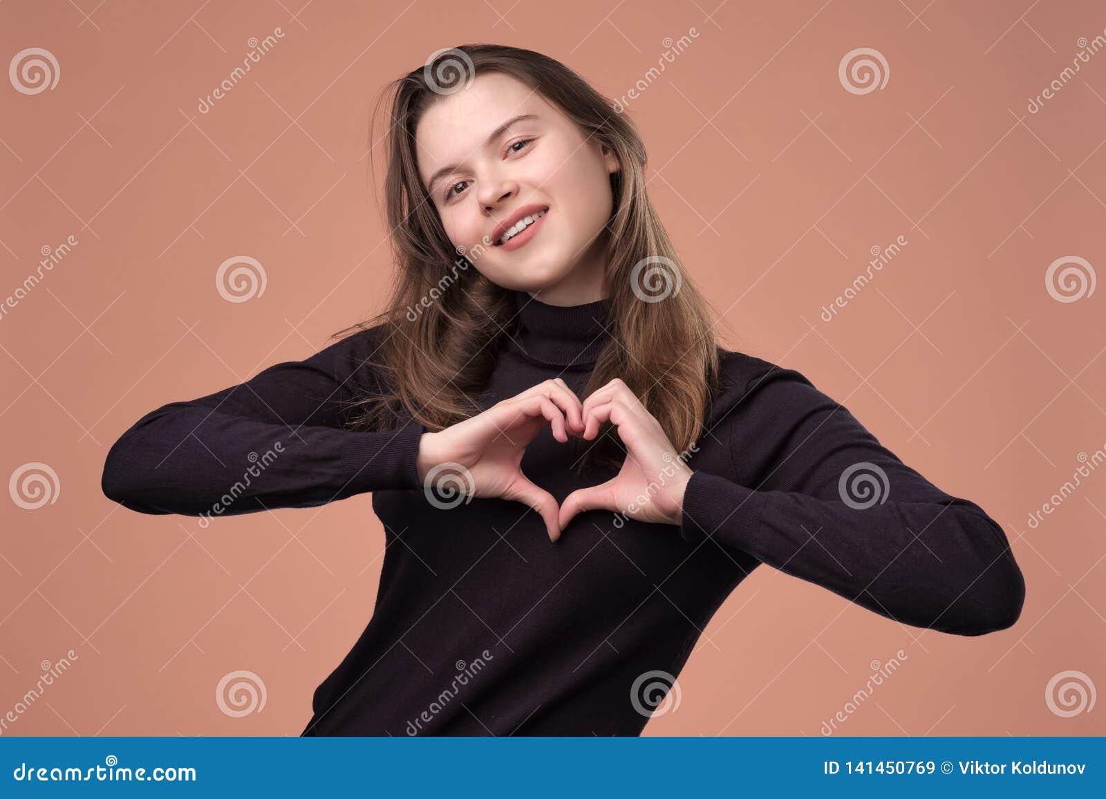 Het gelukkige meisje toont hartgebaar bekijkend camera, het glimlachen