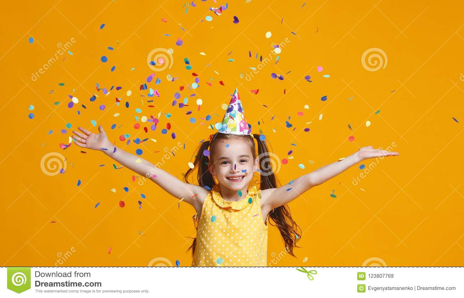 Het gelukkige meisje van het verjaardagskind met confettien op gele achtergrond