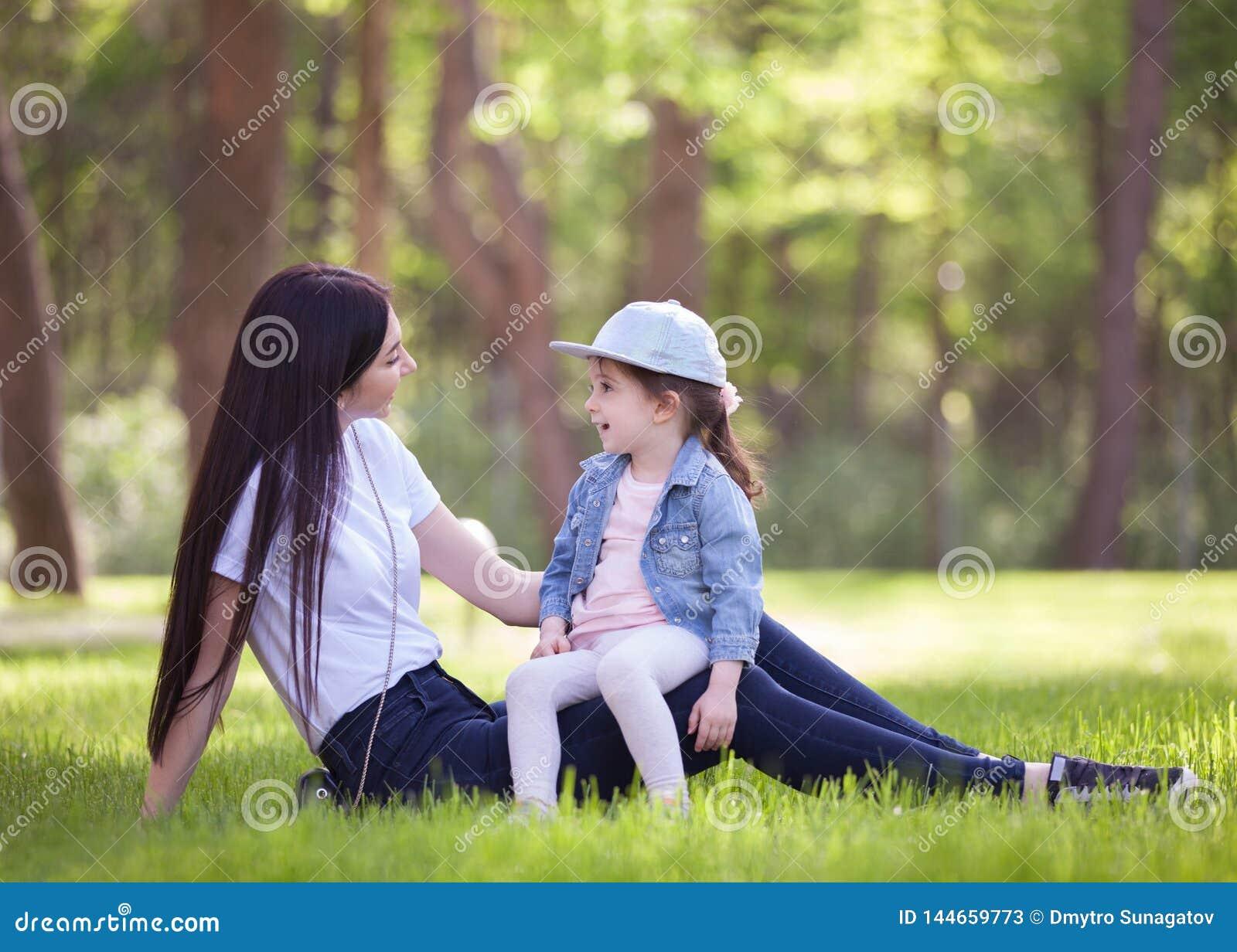 Het gelukkige moeder en dochter ontspannen in het park De scène van de schoonheidsaard met familie openluchtlevensstijl in de le