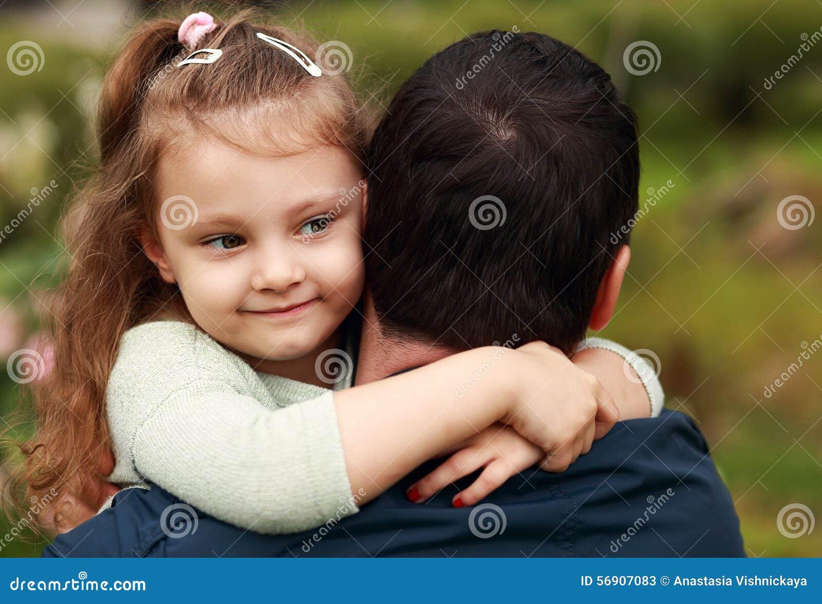 Het gelukkige mooie glimlachende jong geitjemeisje die haar vader met liefde koesteren overtreft