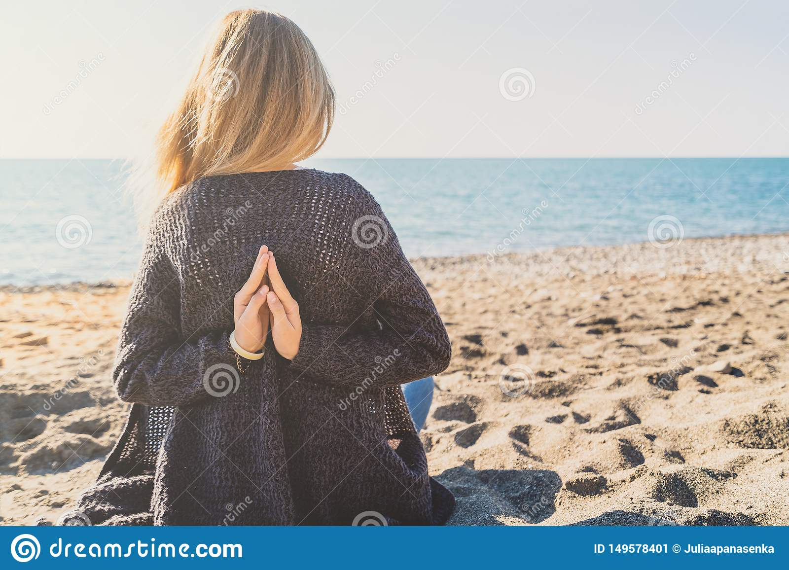 Het gelukkige ontspannen jonge vrouw mediteren in een yoga stelt bij het strand