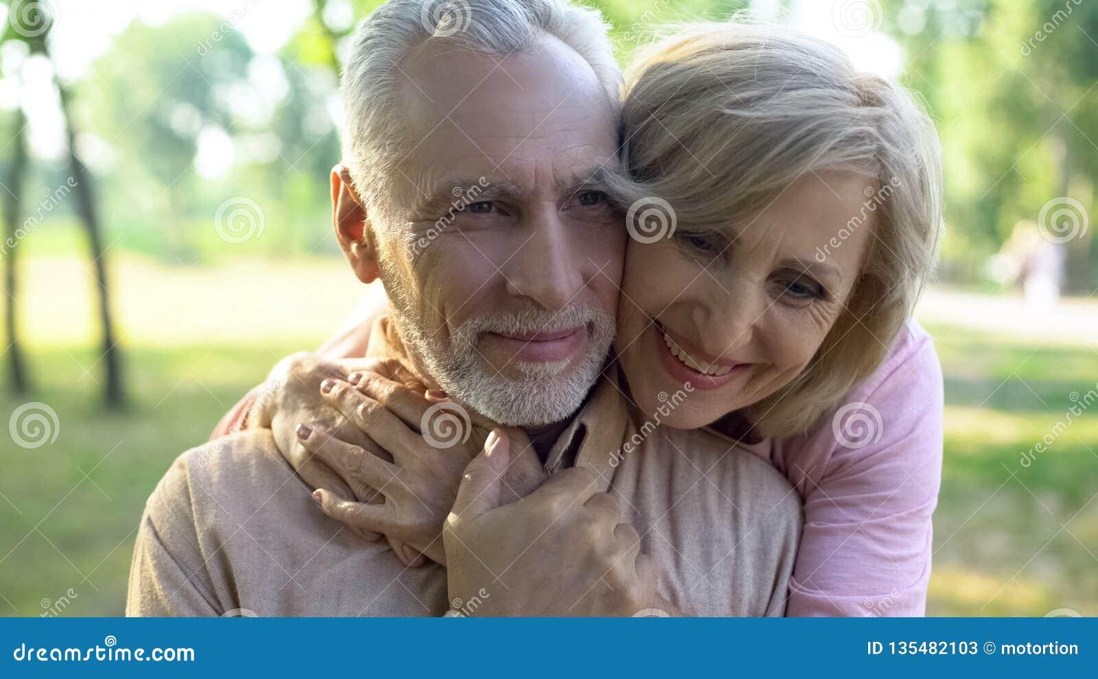 Het gelukkige oude paar koesteren, die in park samen rusten, grootoudersnabijheid