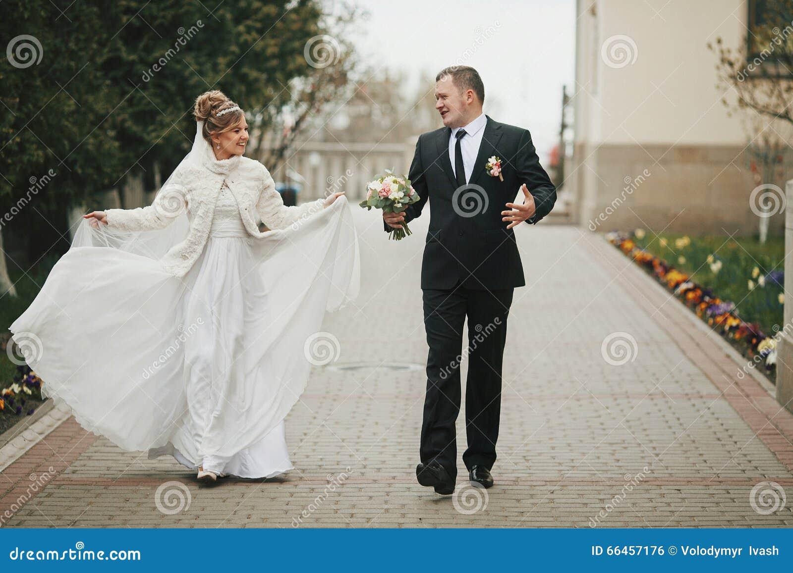 Het gelukkige paar die van het pretjonggehuwde op steegweg lopen in de herfst