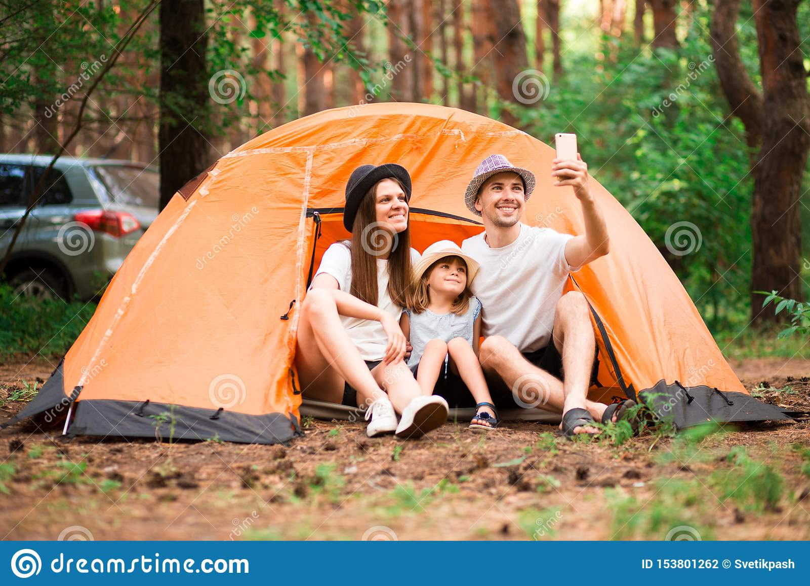 Het gelukkige Portret van de Familie Het kamperen, stijging, technologie en mensenconcept - gelukkige familie die met smartphone