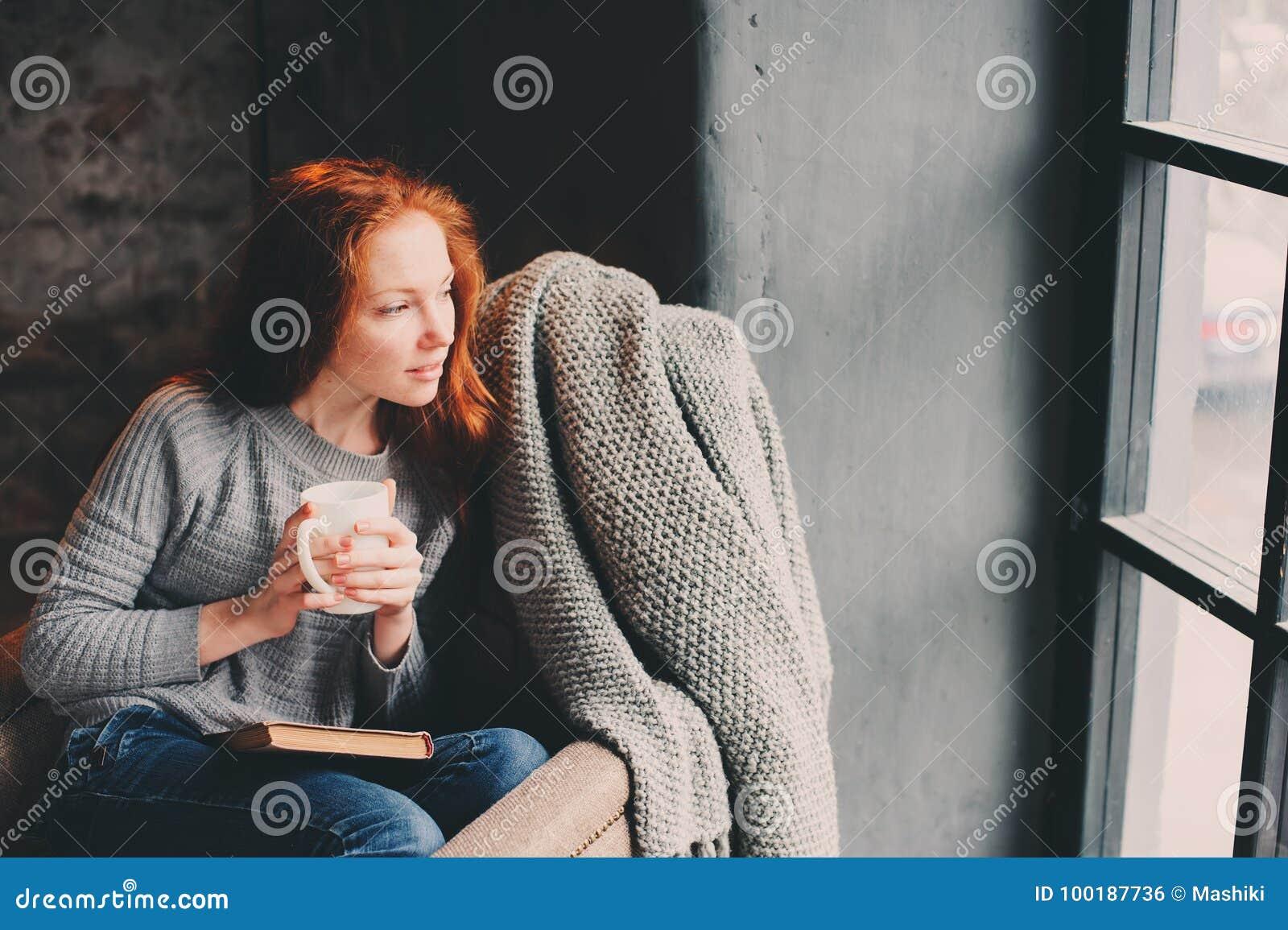 Het gelukkige roodharigevrouw ontspannen thuis in comfortabel de winter of de herfstweekend met boek en kop die van hete thee, al