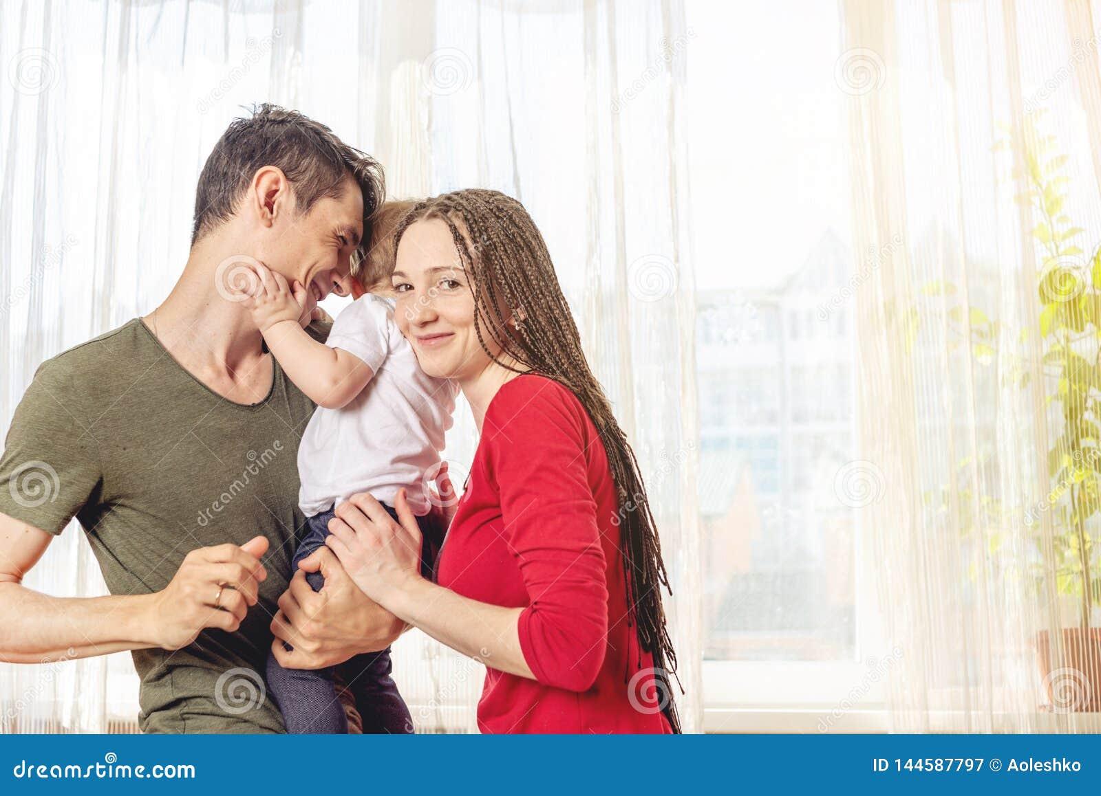 Het gelukkige van de oudersvader en moeder spelen met babyzoon bij de binnen ochtend op vensterachtergrond Vrolijke jonge familie