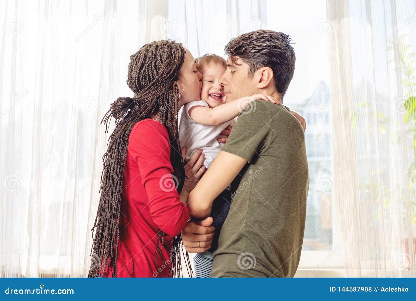 Het gelukkige van de oudersvader en moeder spelen met babyzoon bij de vensterachtergrond Vrolijke en moderne jonge familie