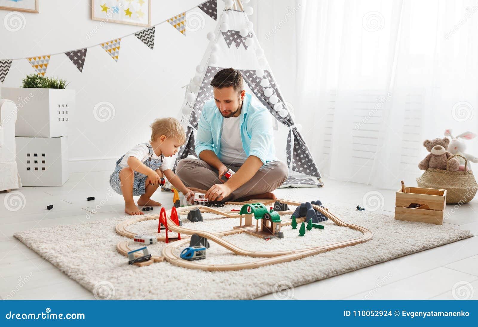 Het gelukkige van het familievader en kind zoon spelen in stuk speelgoed spoorweg in pl