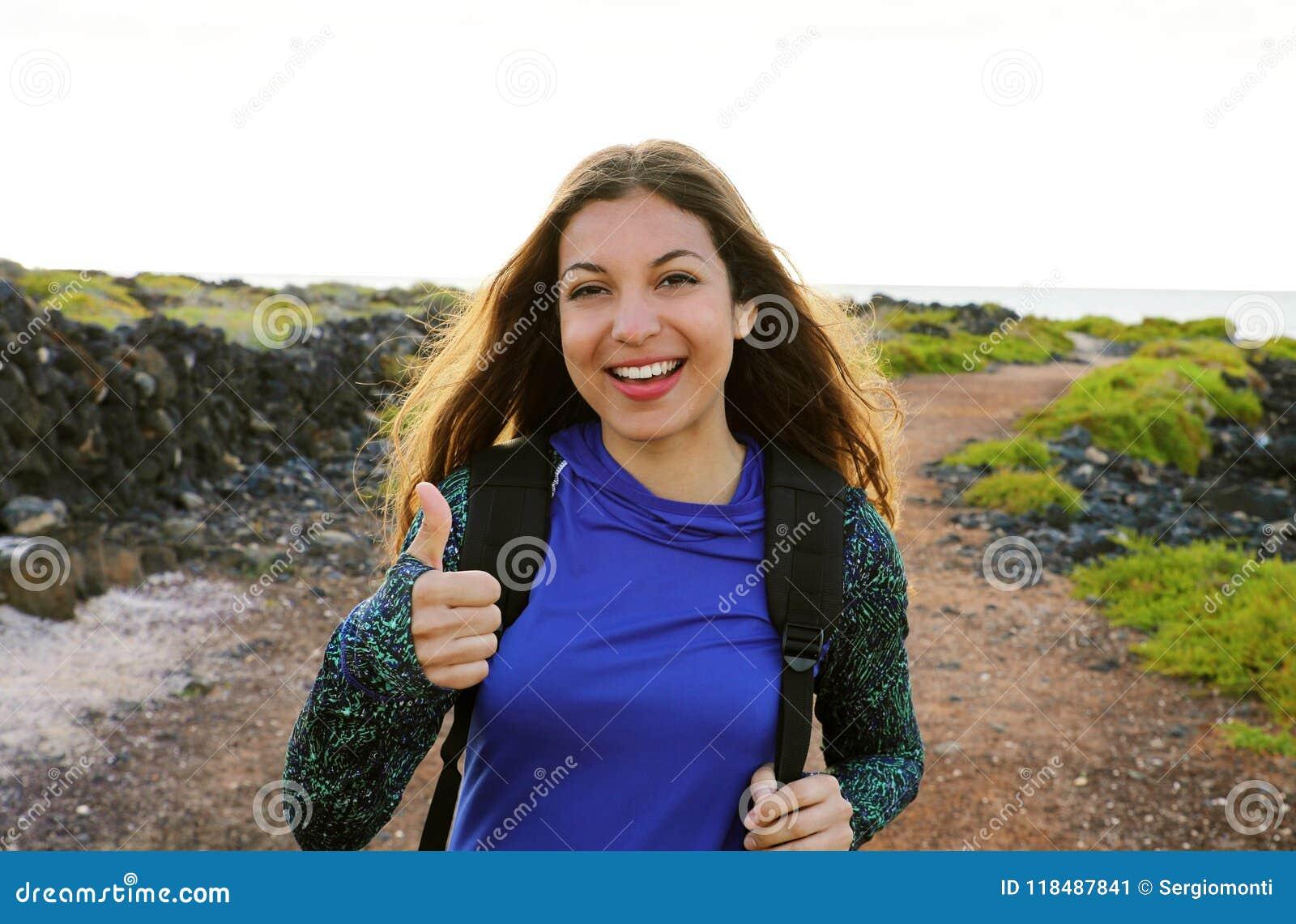 Het gelukkige wandelingsvrouw geven beduimelt omhoog het glimlachen Het jonge wandelaarvrouw glimlachen blij bij camera openlucht