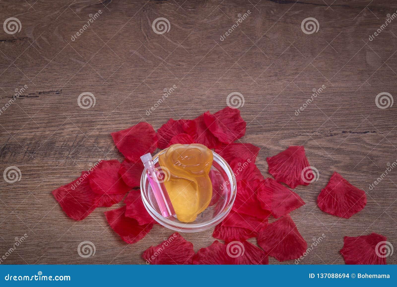 Het geparfumeerde die rozewater en nam bloem van zeep in glaswerk op houten lijst wordt gemaakt toe