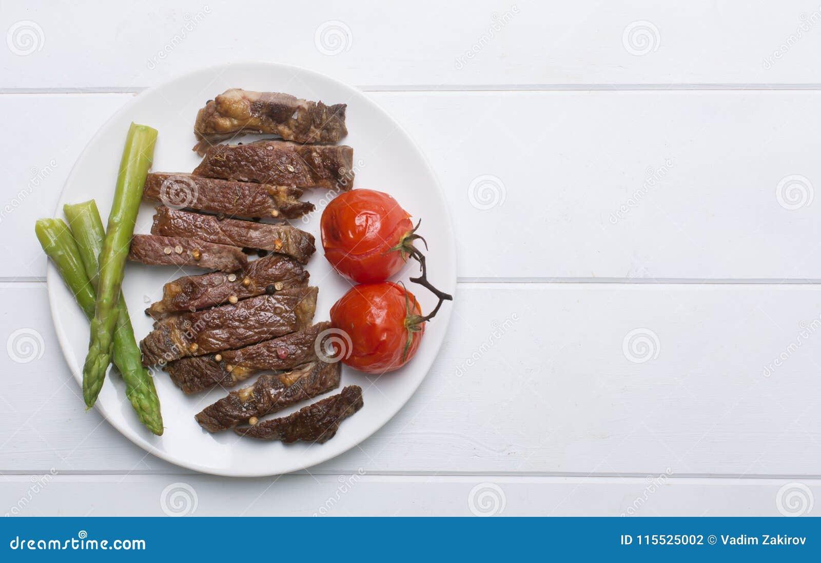 Het geroosterde rundvleeslapje vlees op een witte plaat en een witte achtergrond, vlakte legt en kopieert ruimte