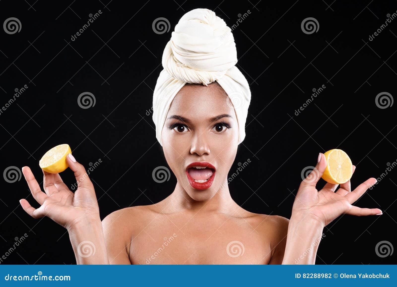 Het geschokte mulatmeisje houdt citroenen