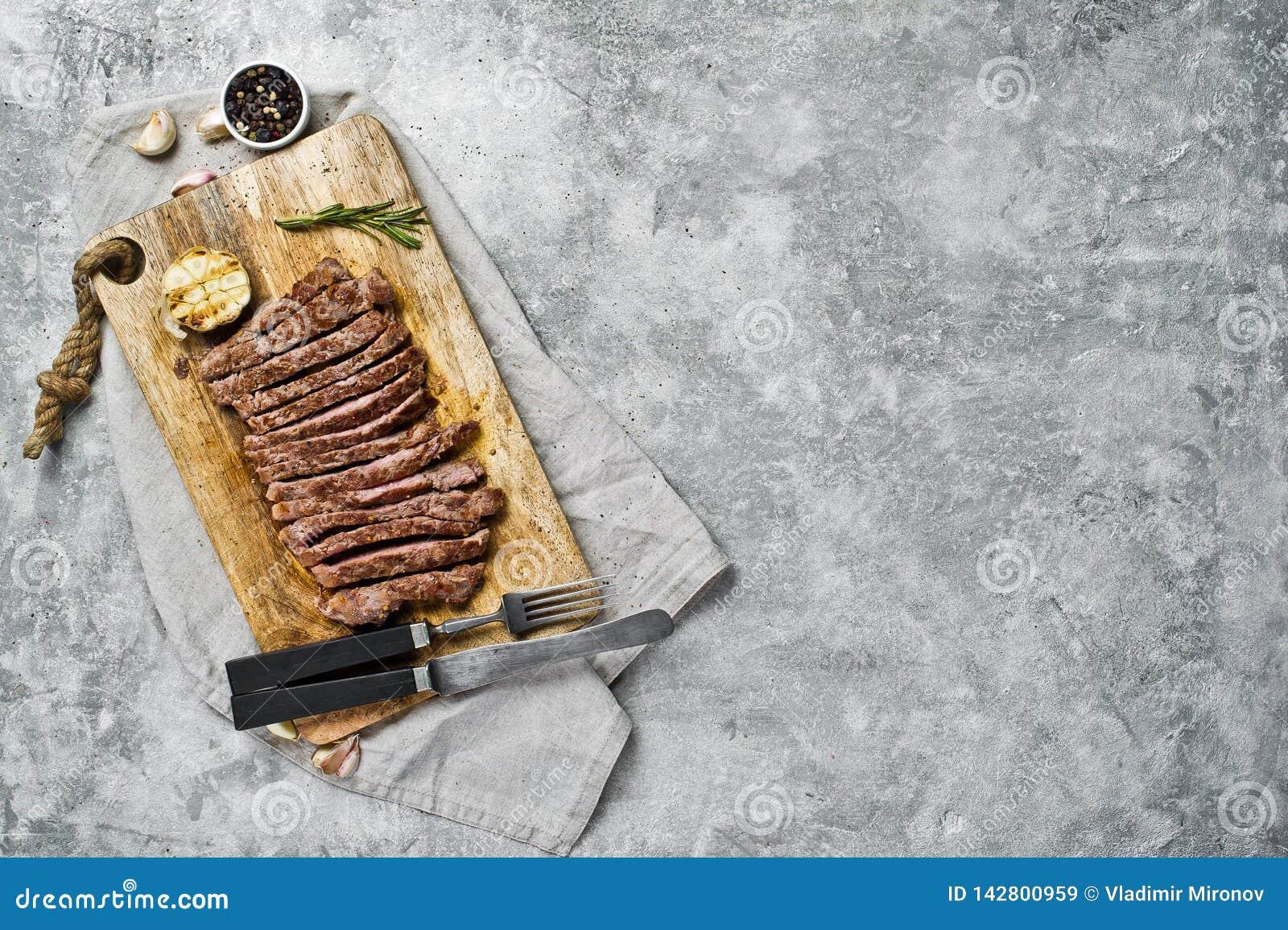 Het gesneden lapje vlees van de rundvleesflank op houten Hakbord Grijze achtergrond, hoogste mening, ruimte voor tekst