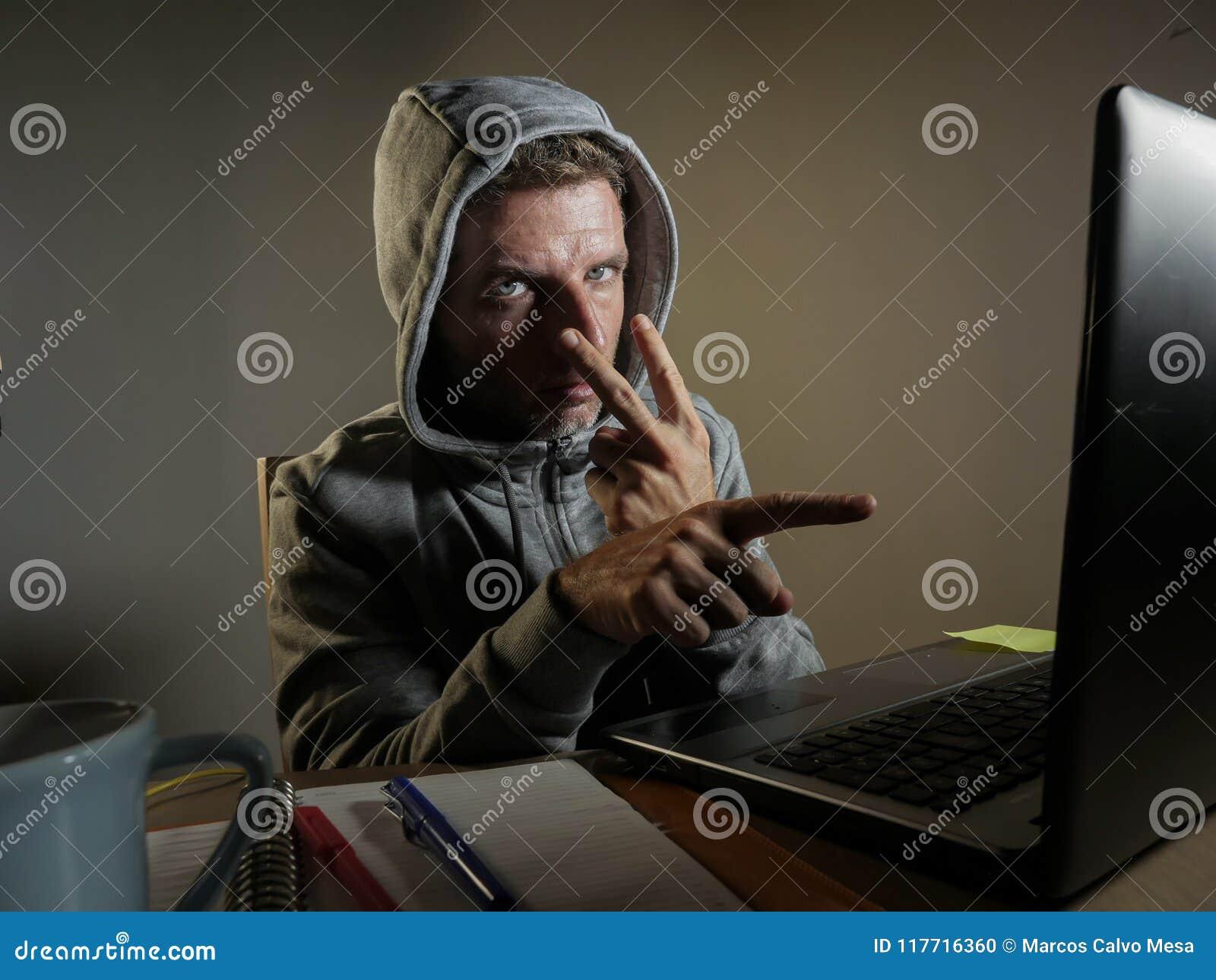 Het gevaarlijke kijken hakkermens die in hoodie het computersysteem die van Internet binnendringen in een beveiligd computersyste