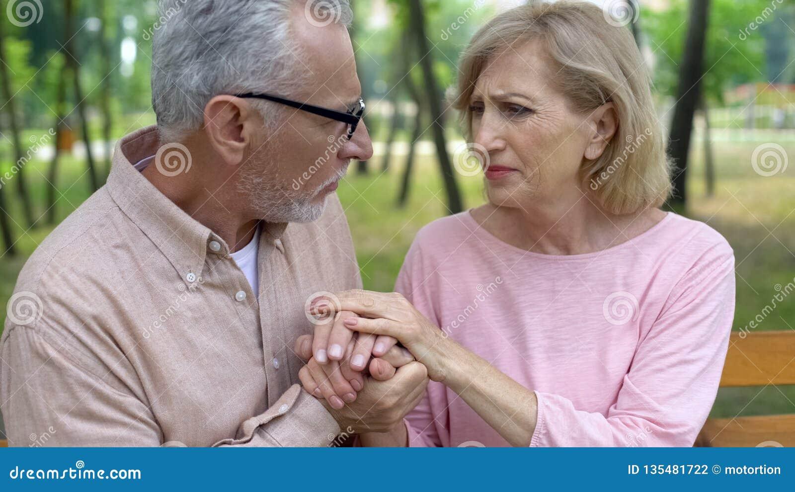 Het geven de handen van de echtgenootholding van oude zieke vrouw, de ziekte van Alzheimer, familiesteun