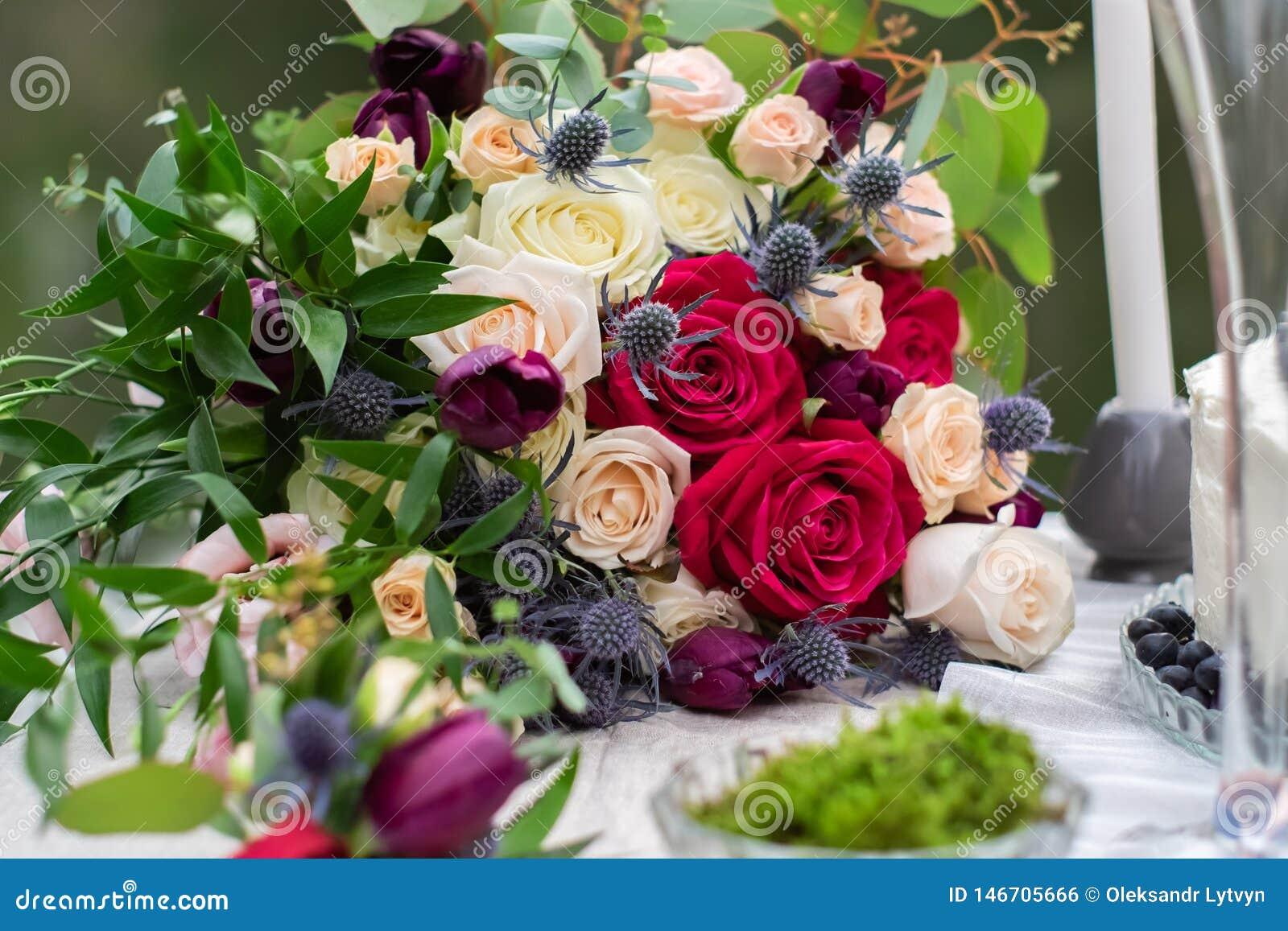 Het gevoelige huwelijksboeket met de room roze rozen van Bourgondi? en feverweed, close-up