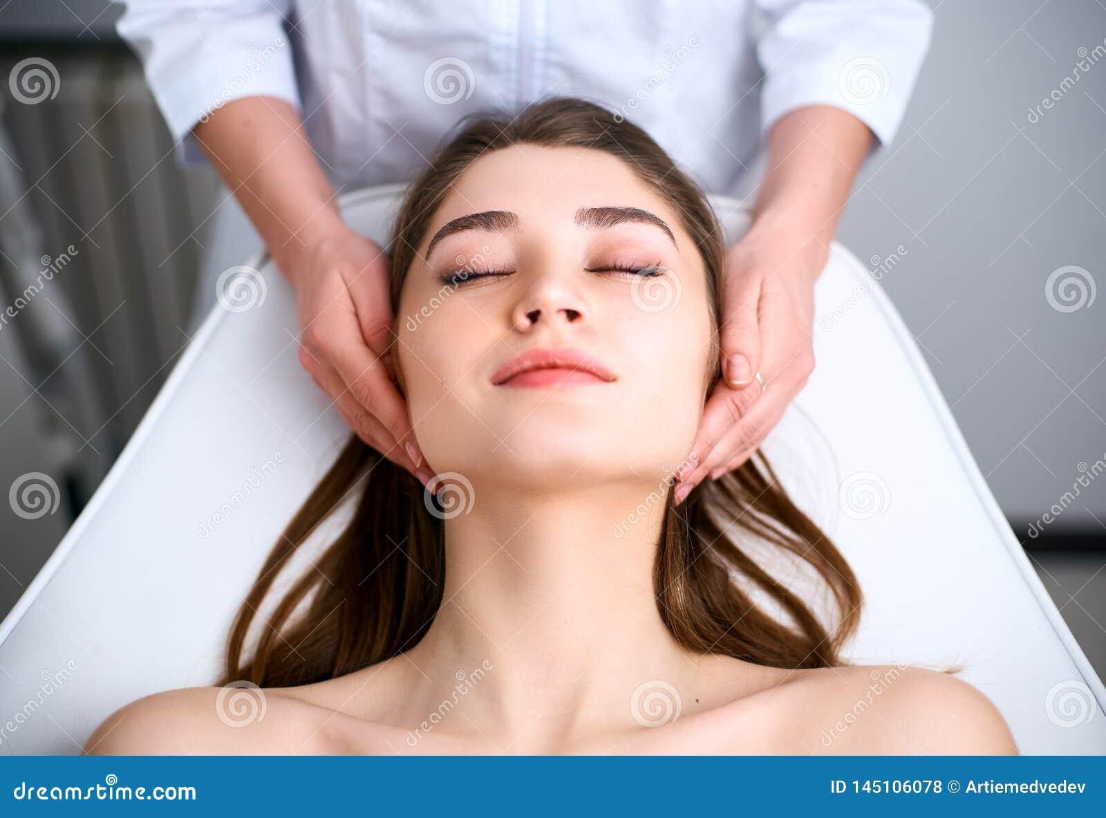 Het gezicht van de schoonheidsspecialist schoonmaakster Kuuroord skincare behandeling Cosmetologist met pati?nt op medische stoel
