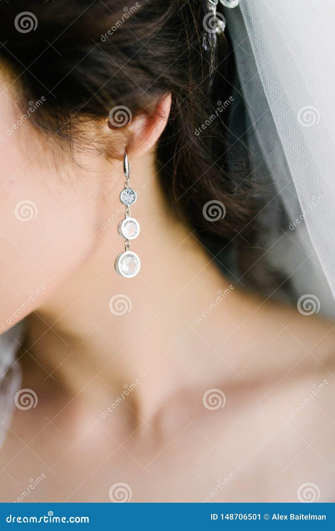 Het gezicht van een jonge vrouw met grote oorringen sluit omhoog