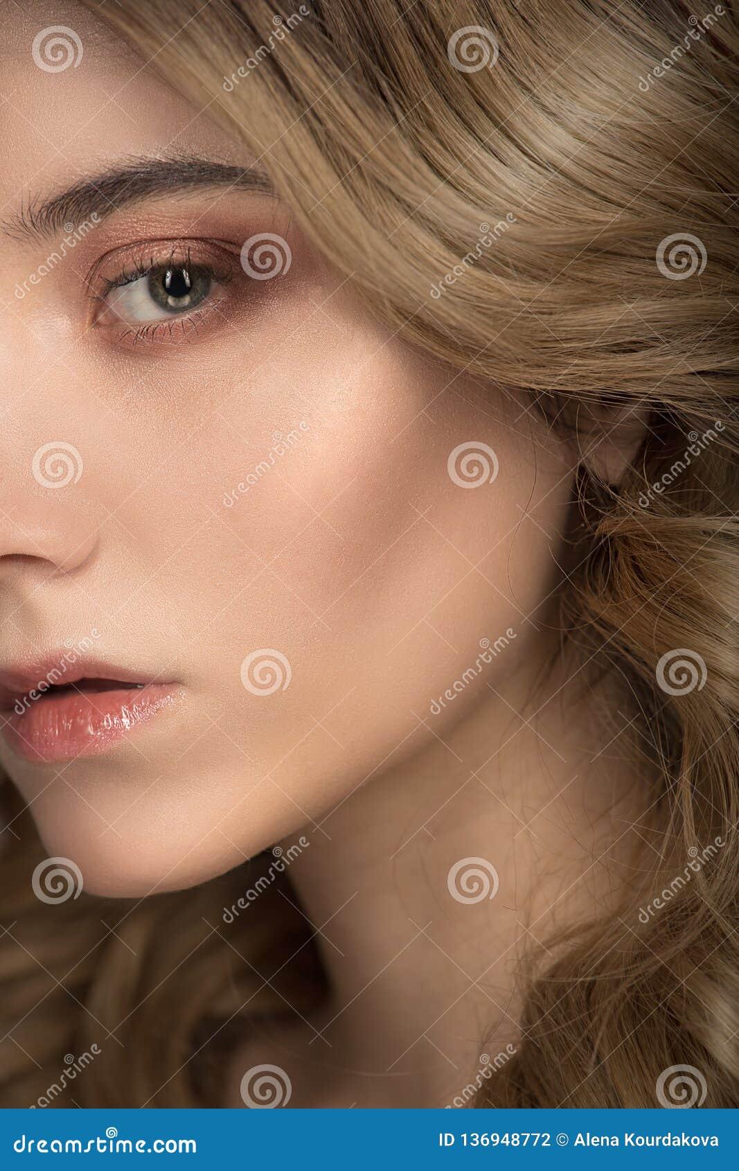 Het gezichtsclose-up van de maniervrouw Schitterings golvende haar en make-up