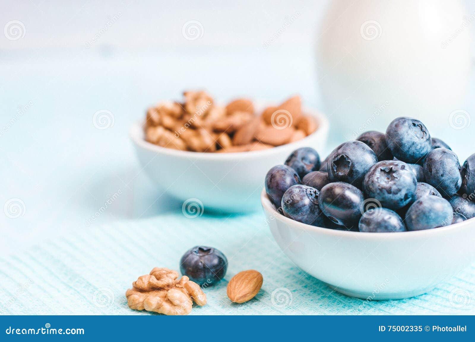 Het gezonde ontbijt, de bosbes en de melk, noten, amandel met close-up van de tekst het ruimte hoogste mening instagram filtreren