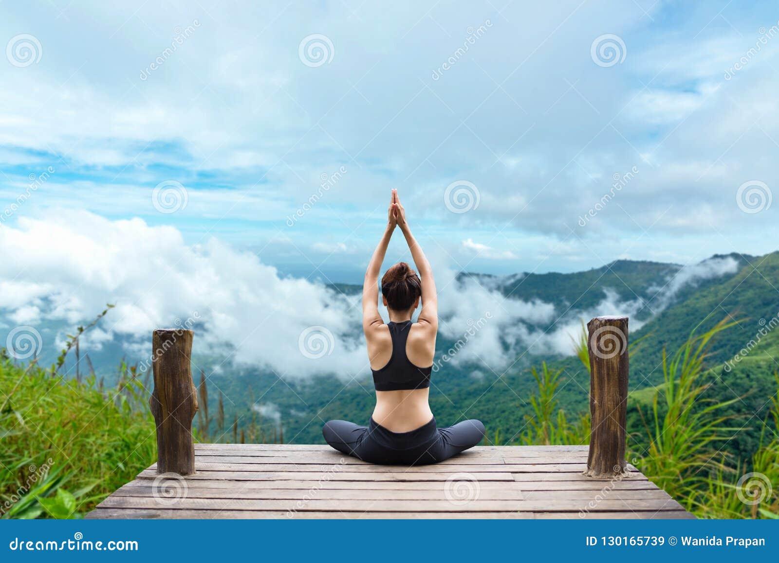 Het gezonde vrouw levensstijl evenwichtige praktizeren mediteren en zen de energieyoga op de brug in ochtend de bergaard