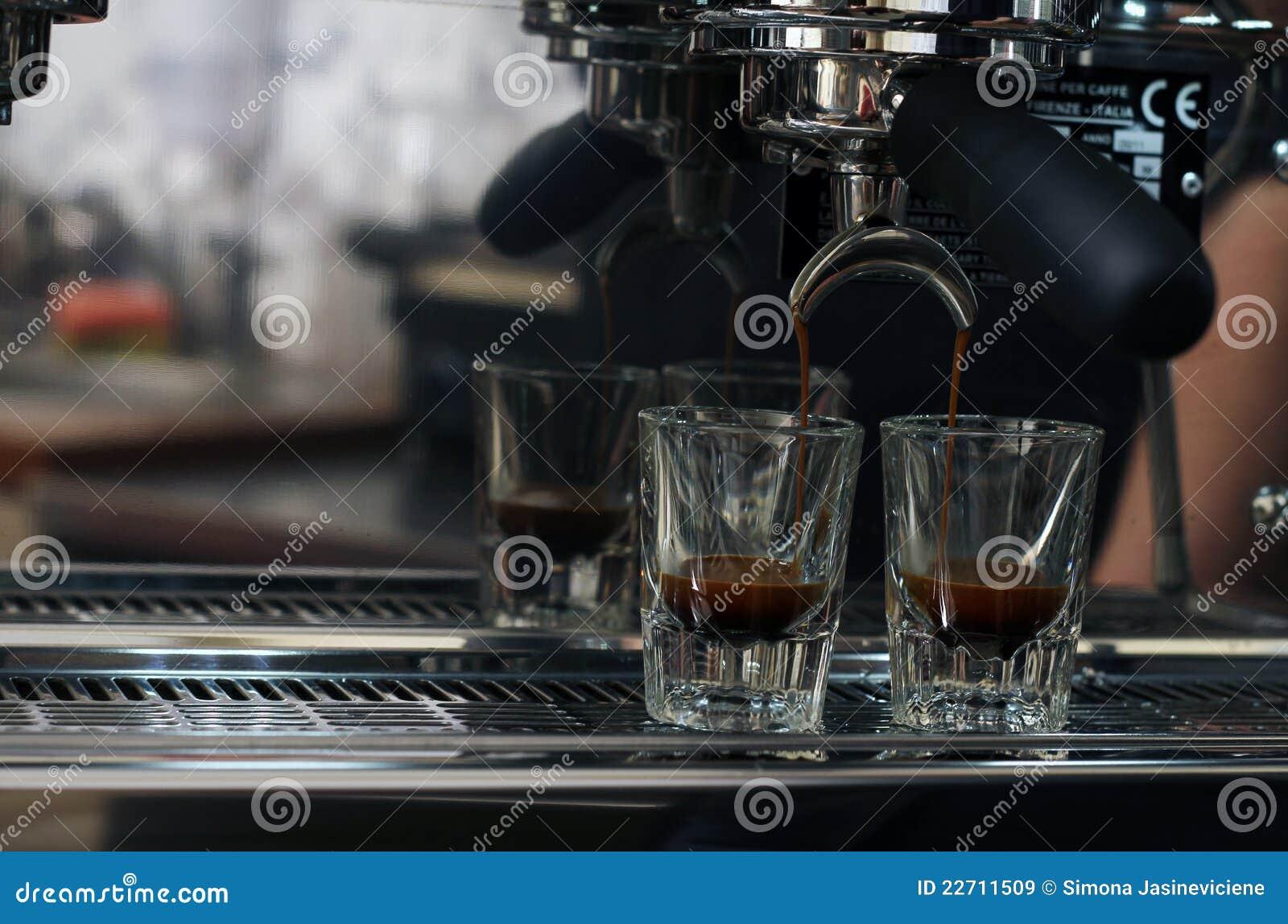 Het gieten van de espresso in twee ontsproten glazen