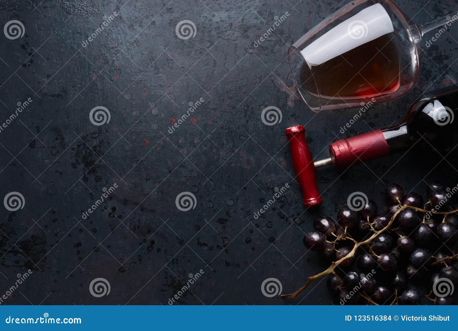 Het glas met rode wijn, fles met kurketrekker en rode druif groepeert zich op zwarte rustieke achtergrond, hoogste mening plaats