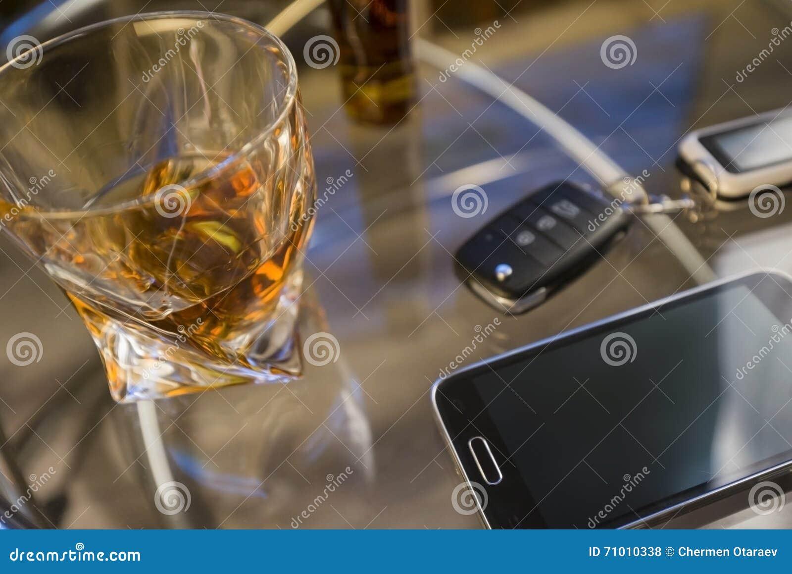 Het glas van alcoholische drank en de auto sluiten, op de lijst, lichte achtergrond