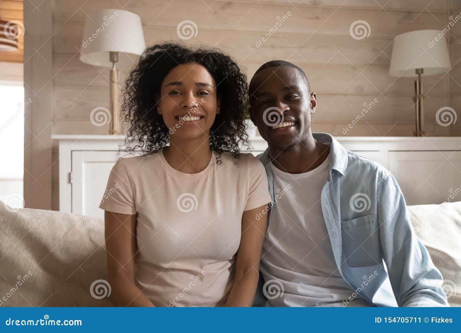 Het glimlachen Afrikaanse paarzitting die op laag videogesprek maken