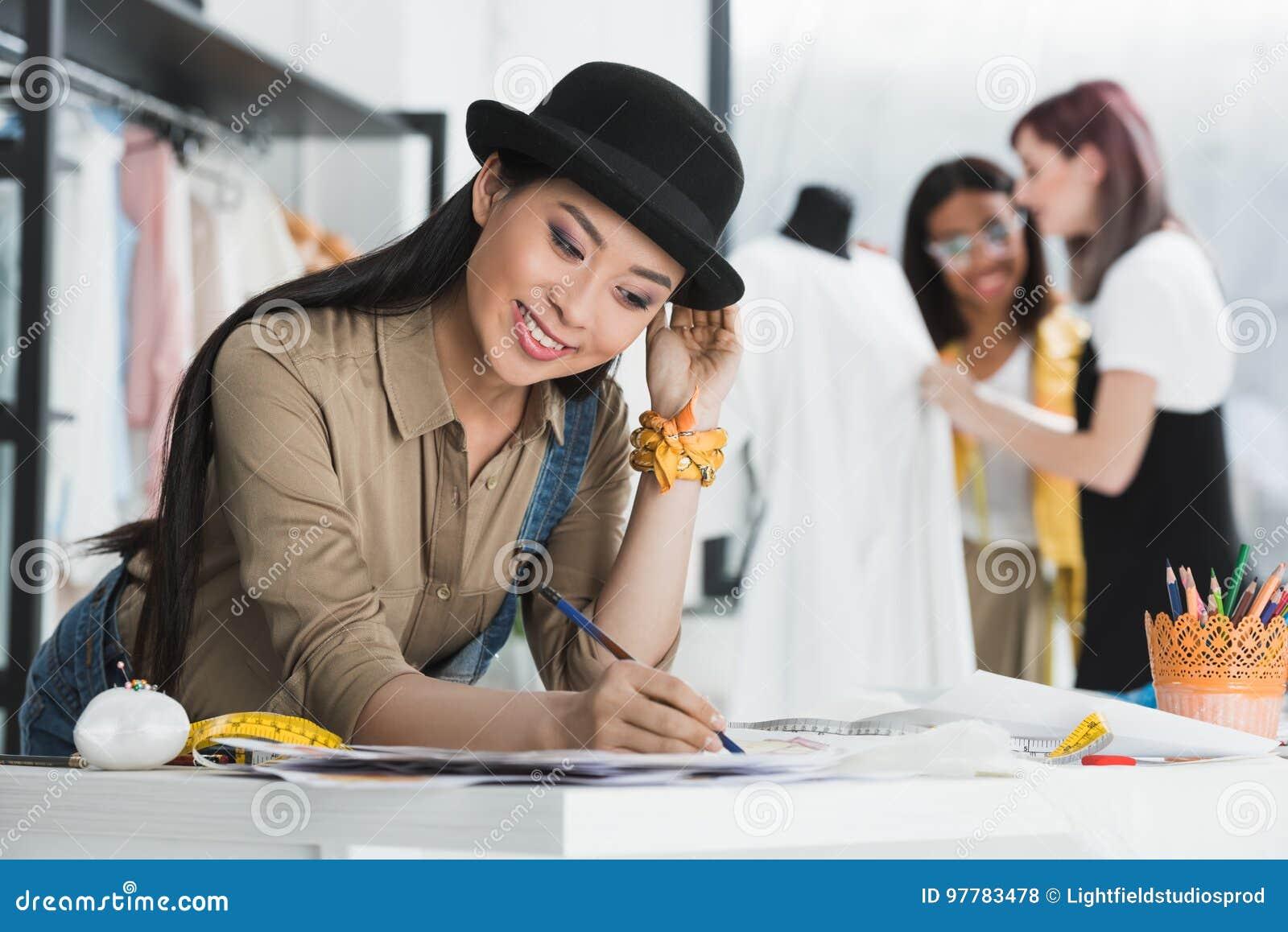 Het glimlachen Aziatische de tekeningsschetsen van de manierontwerper terwijl collega s die erachter werken