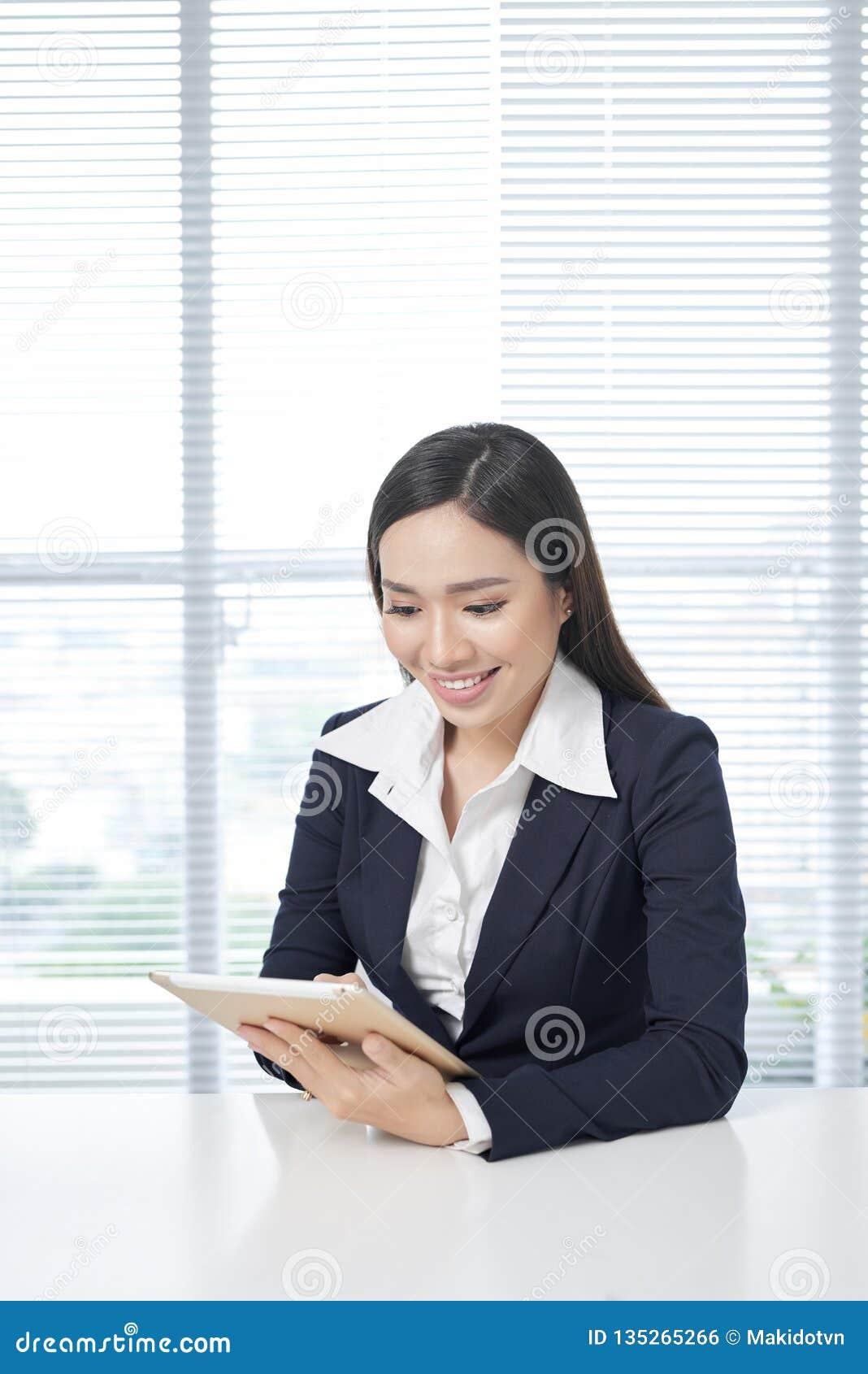 Het glimlachen Aziatische onderneemsterzitting in helder bureau