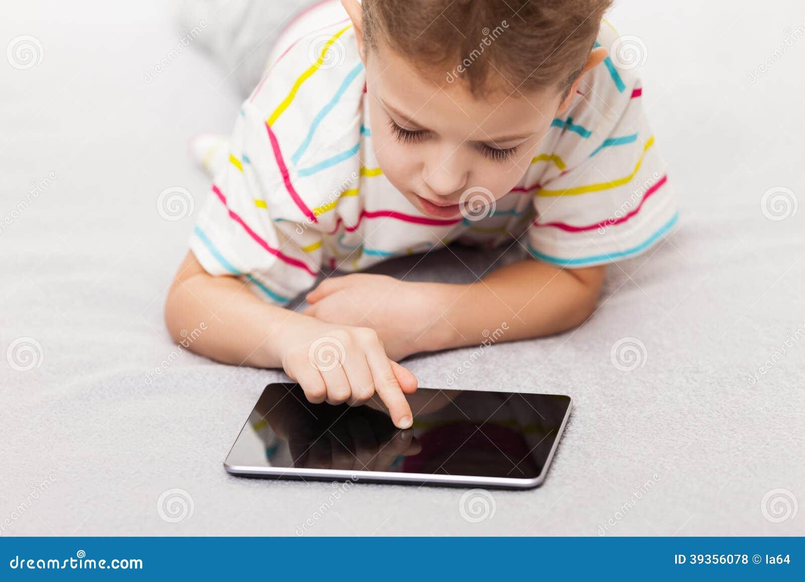 Het glimlachen de speelspelen van de kindjongen of surfend Internet op mede tablet