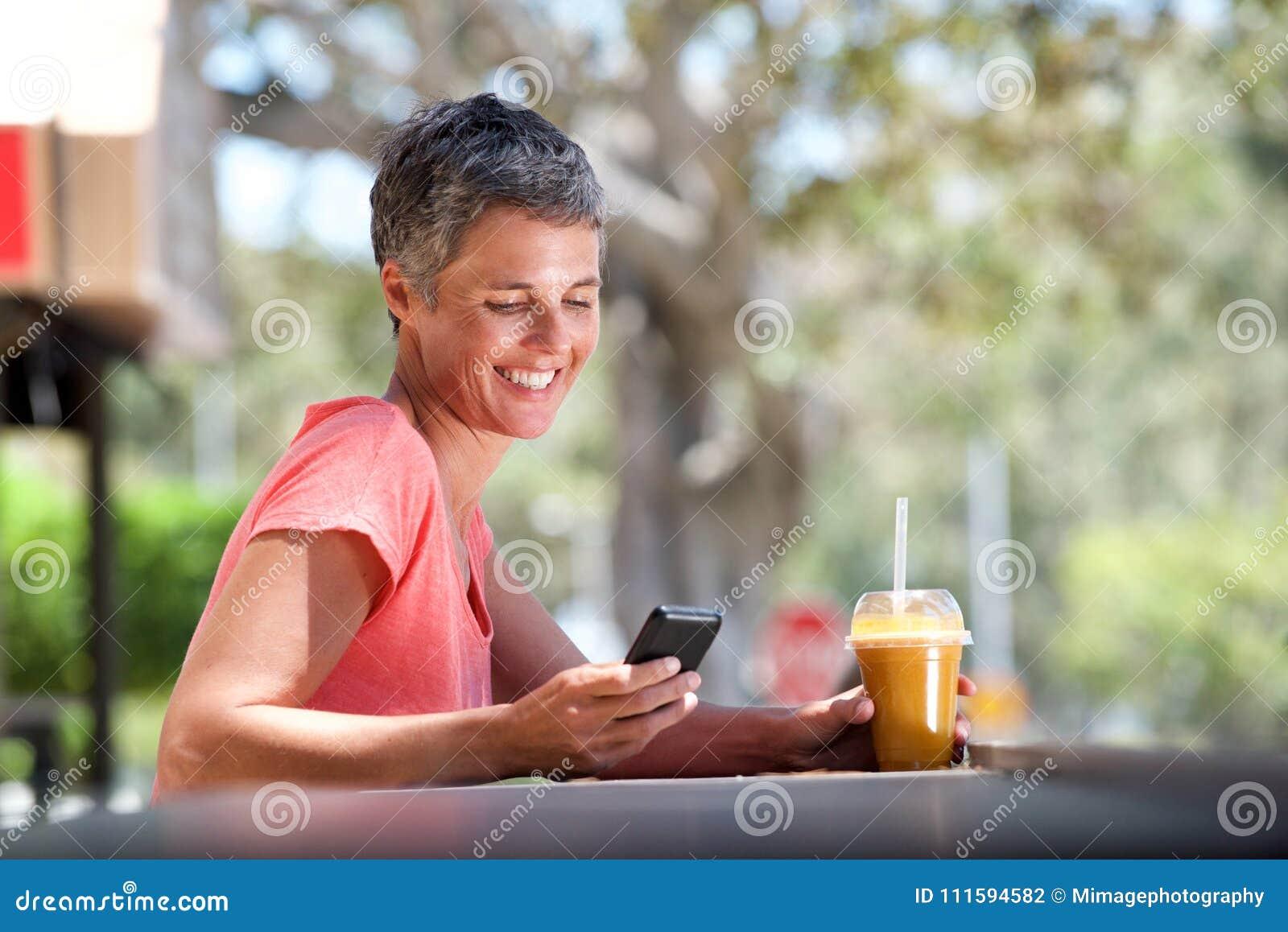 Het glimlachen de zitting van de middenleeftijdsvrouw buiten met mobiele telefoon en drank