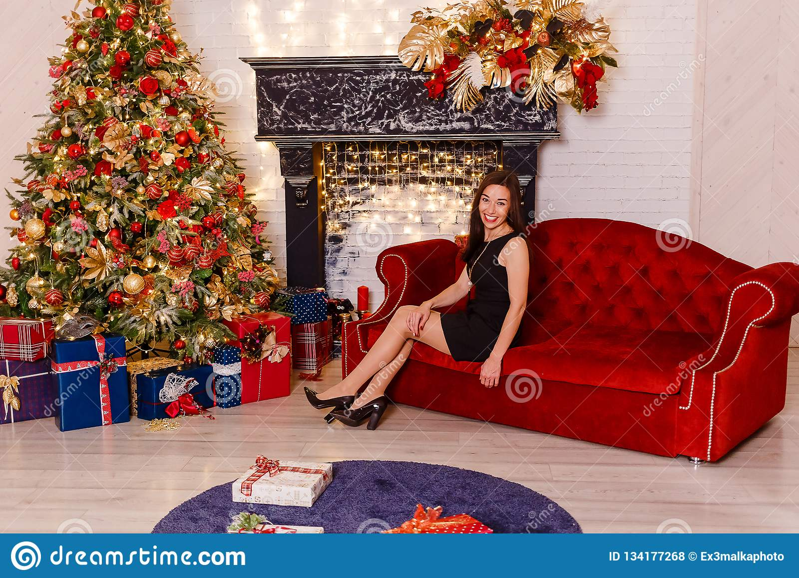Het glimlachen jonge vrouwenzitting op een rode laag op Kerstmis