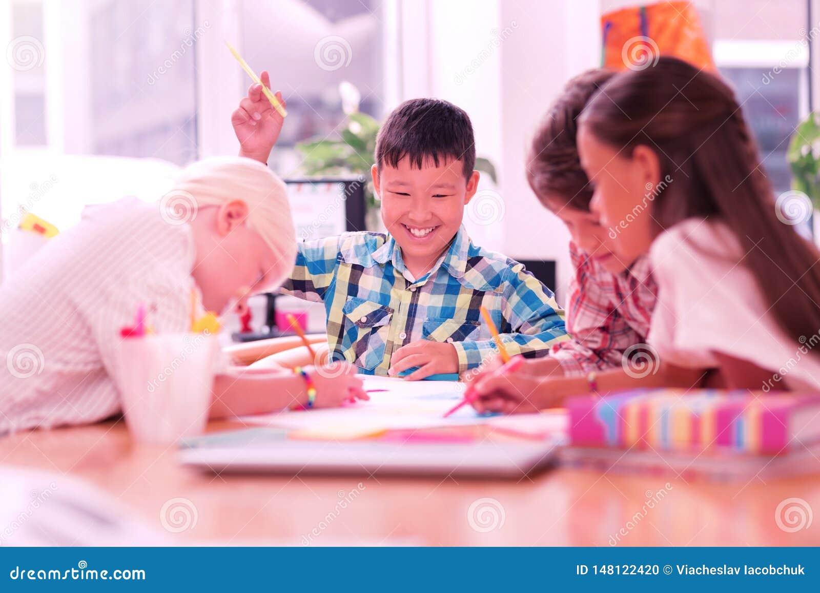 Het glimlachen jongenszitting onder zijn tekeningsvrienden
