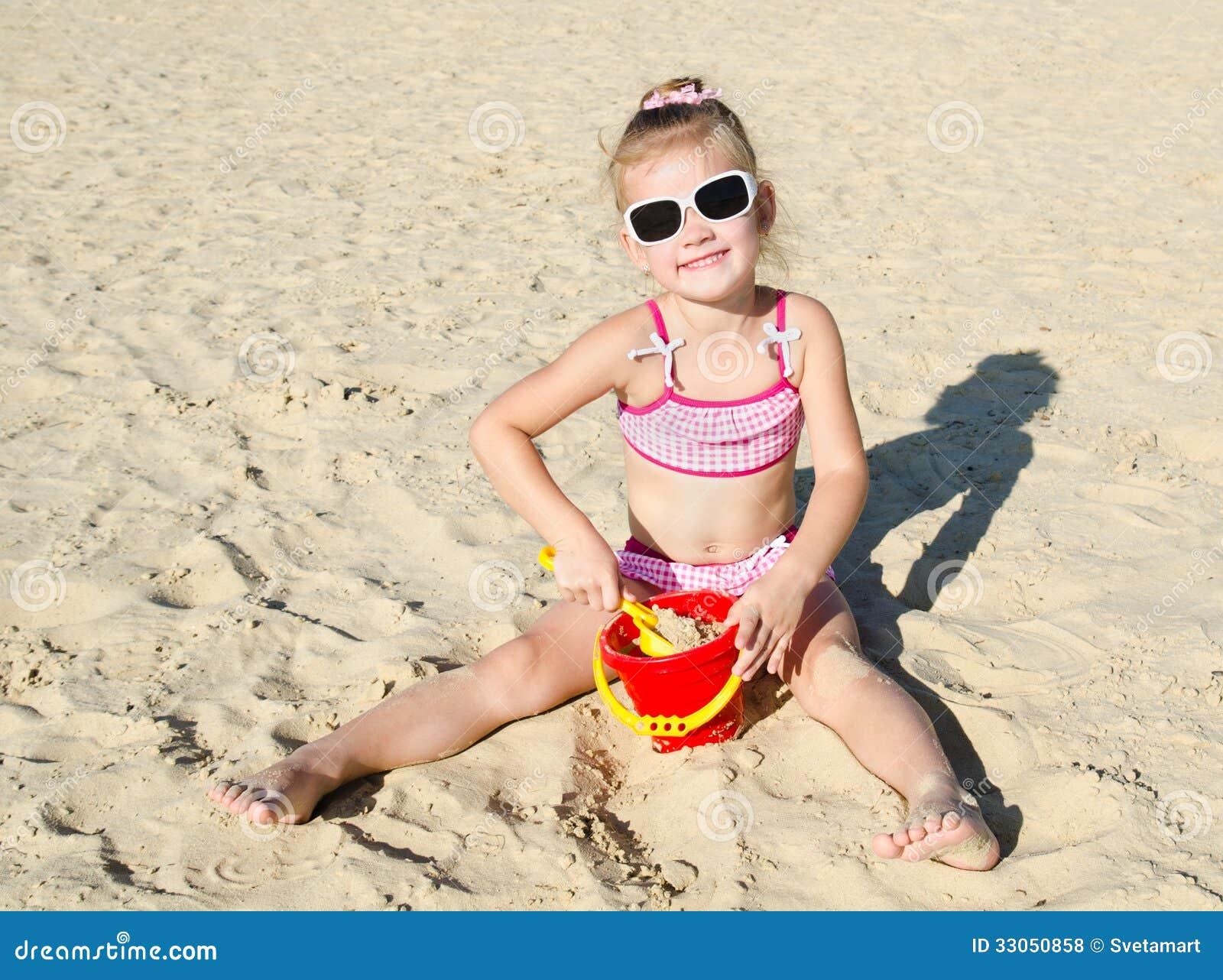 Het glimlachen meisje het spelen op strand