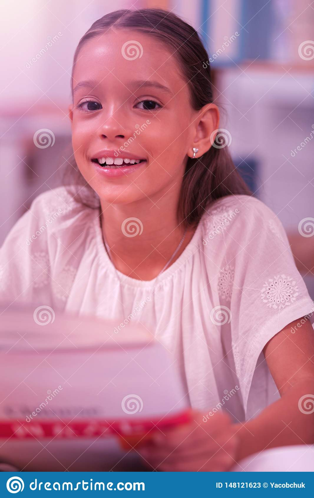 Het glimlachen meisjeszitting bij de schoolbank