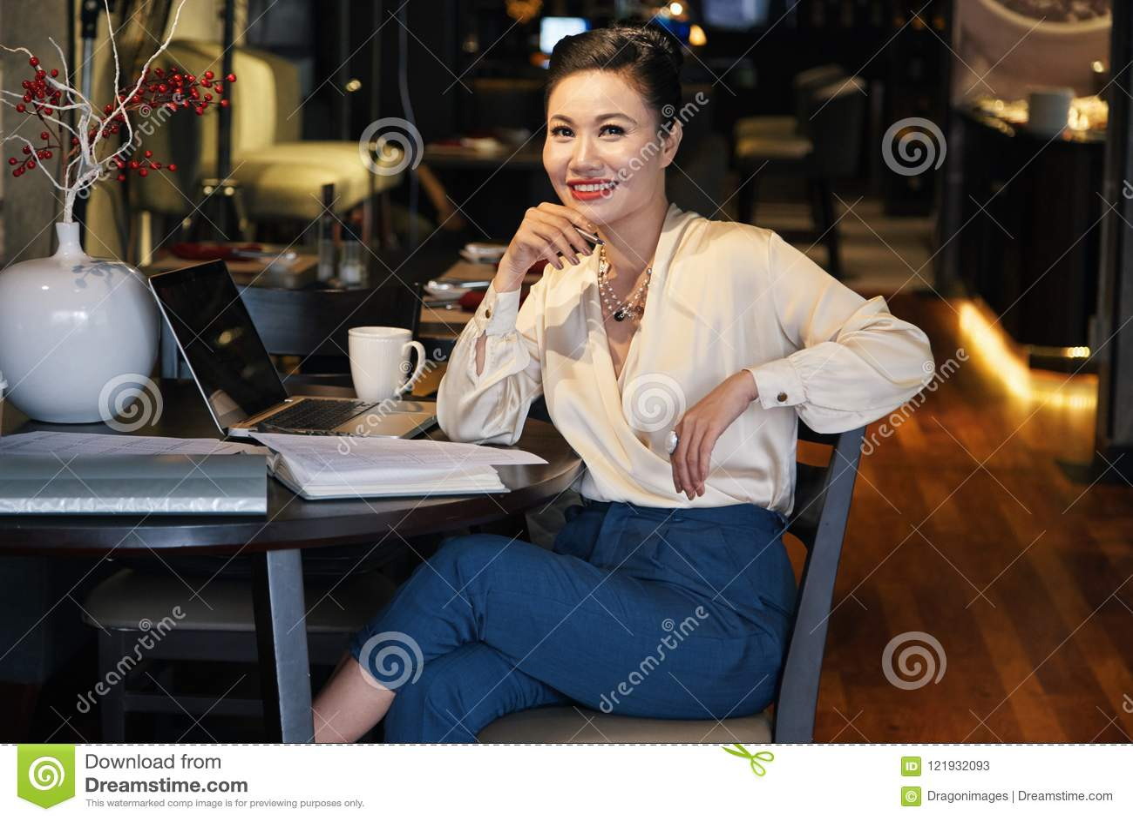 Het glimlachen ontspande Aziatische onderneemsterzitting in koffie