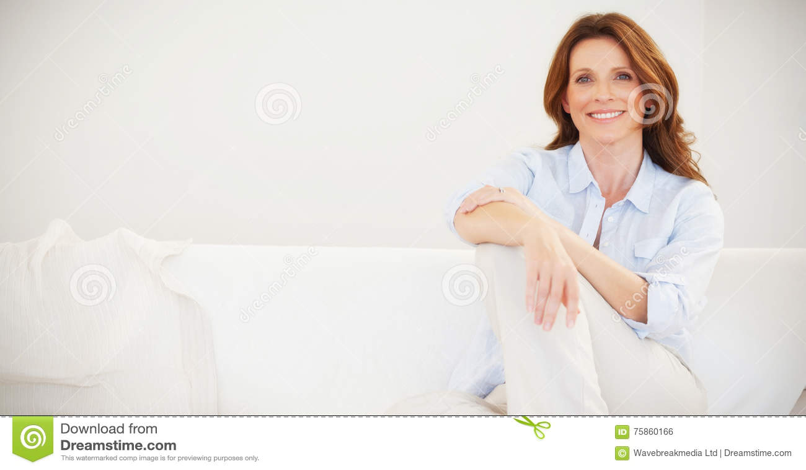 Het glimlachen rijpe vrouwenzitting op bank