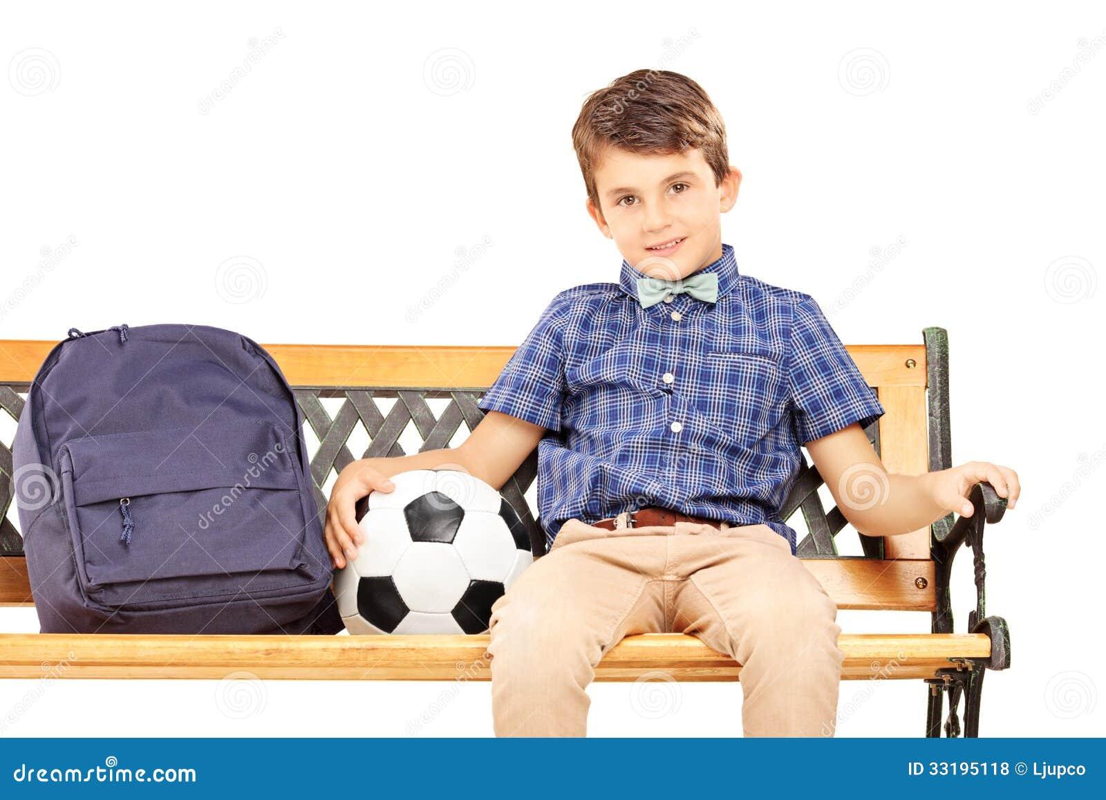 Het glimlachen schooljongenzitting op een bank met schooltas en bal
