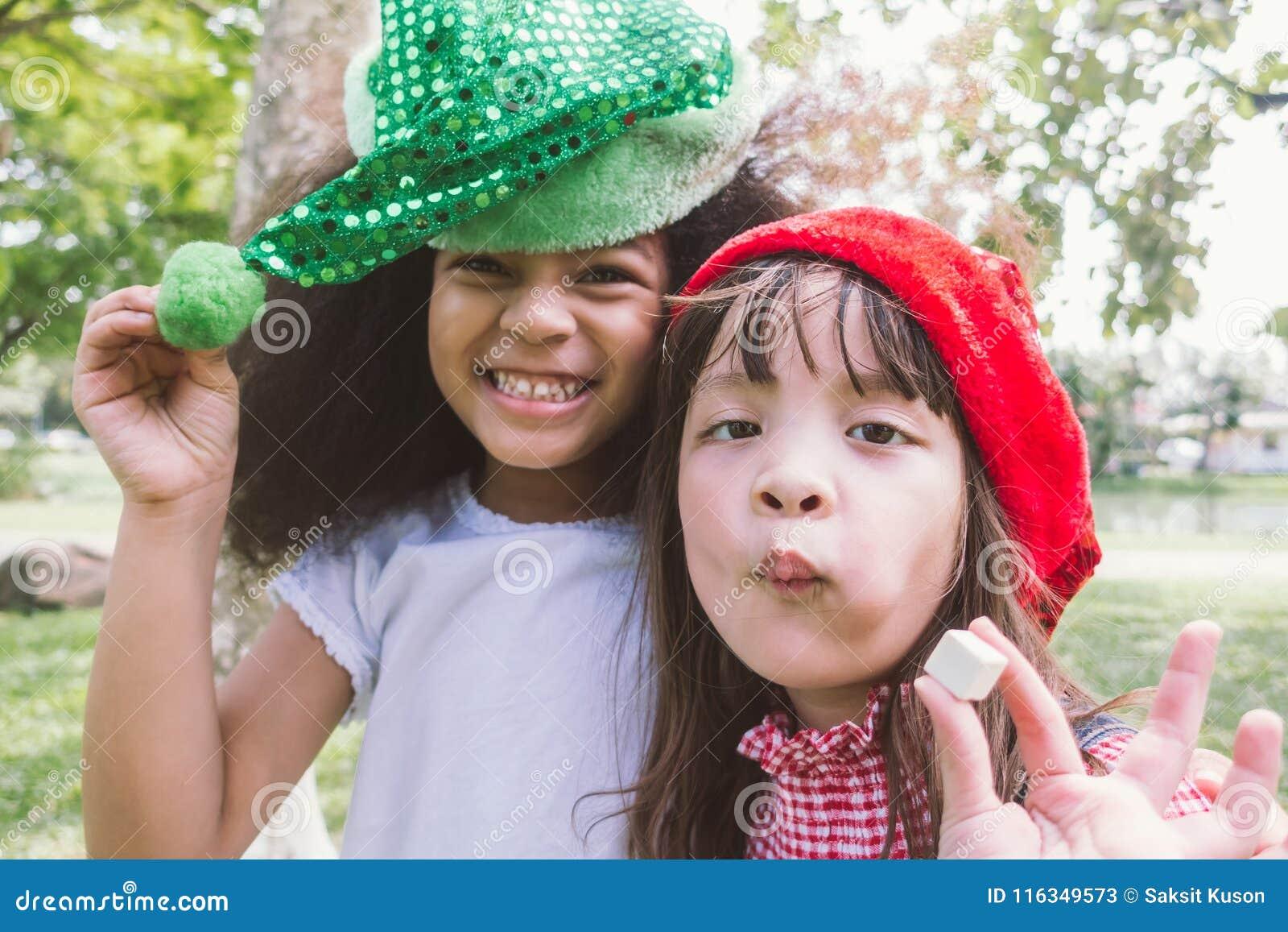 Het glimlachen twee eet de gelukkige de partijhoed van de meisjeslijtage suikergoed