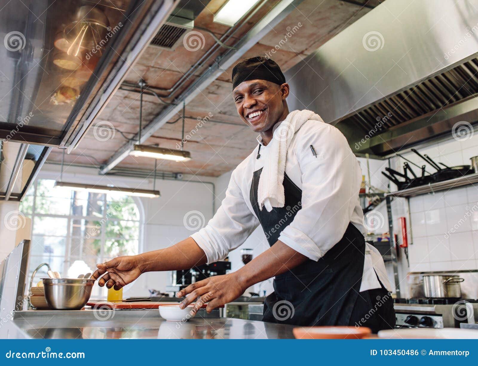 Het glimlachen van chef-kok kokend voedsel bij restaurantkeuken