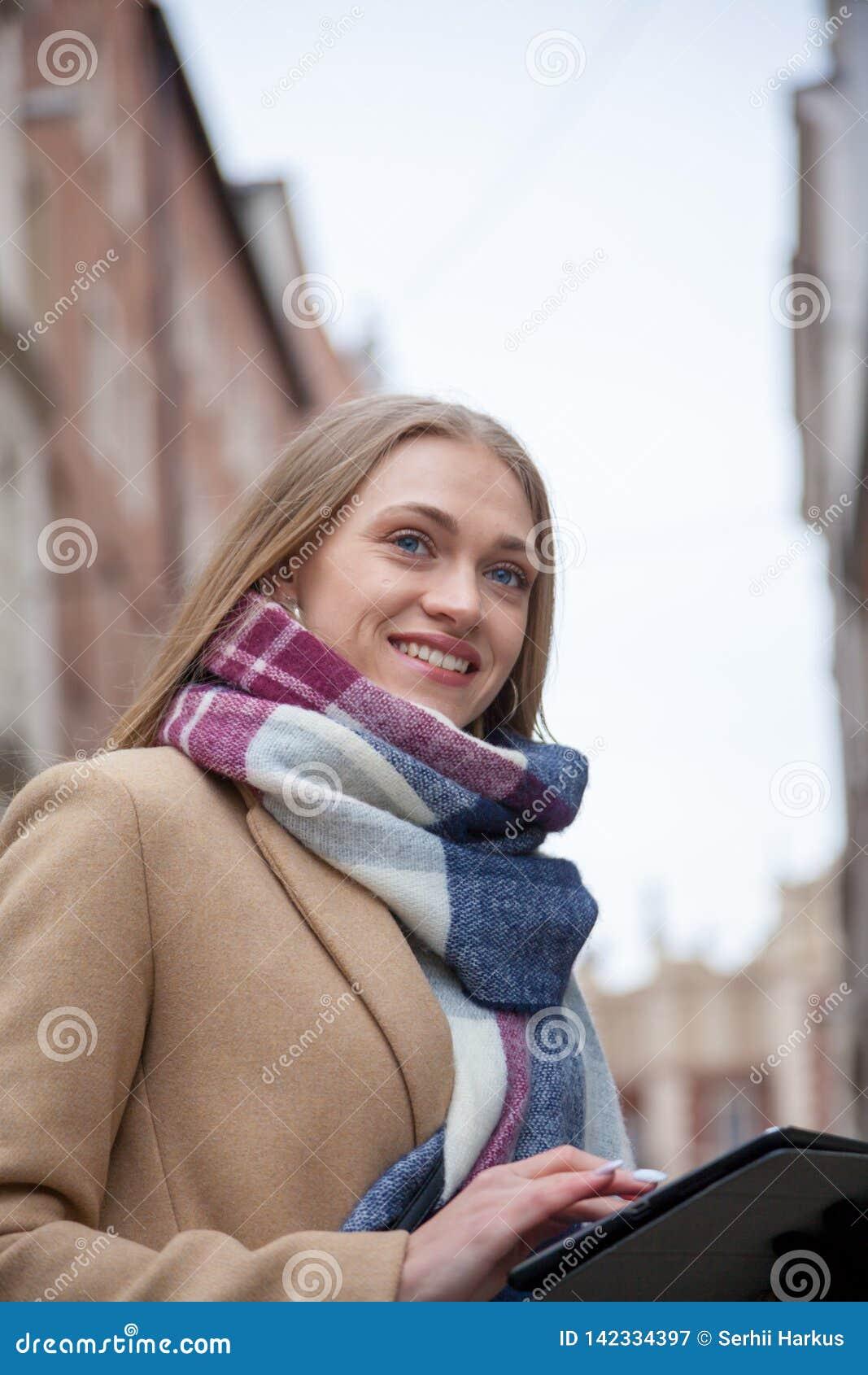 Het glimlachen van de holdingstablet van de blonde mooie vrouw op stadsstraat