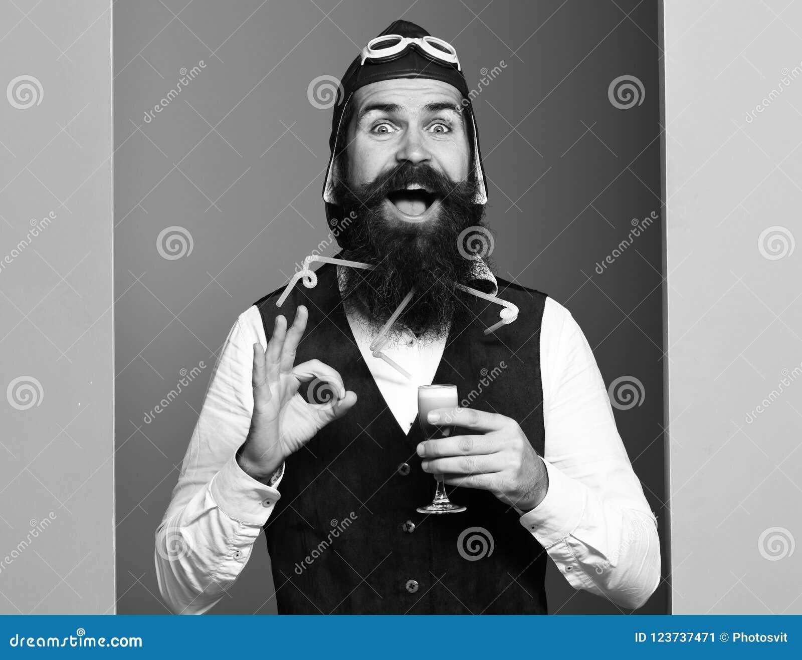 Het glimlachen van het glas van de gezichtsholding van alcoholisch schot in het uitstekende vest van het suèdeleer met hoed en gl