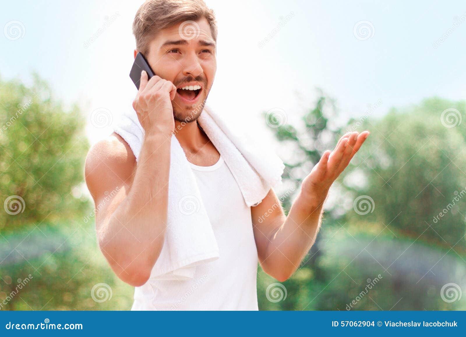 Het glimlachen van kerel die op telefoon spreken